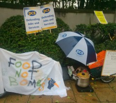 'Food Not Bombs' banner and cycle trailer with food, covered by umbrella.