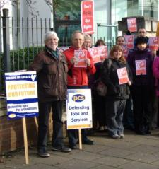 """Pickets with placards reading """"PCS - Defending Jobs and Services"""" and """"Protecting Our Future"""""""
